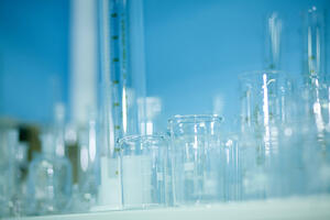 Clear Scientific Beakers and Test Tubes on Blue Background
