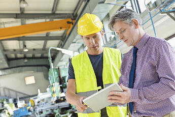 Factory Worker and Manager Looking at Wireless Tablet on Plant Floor