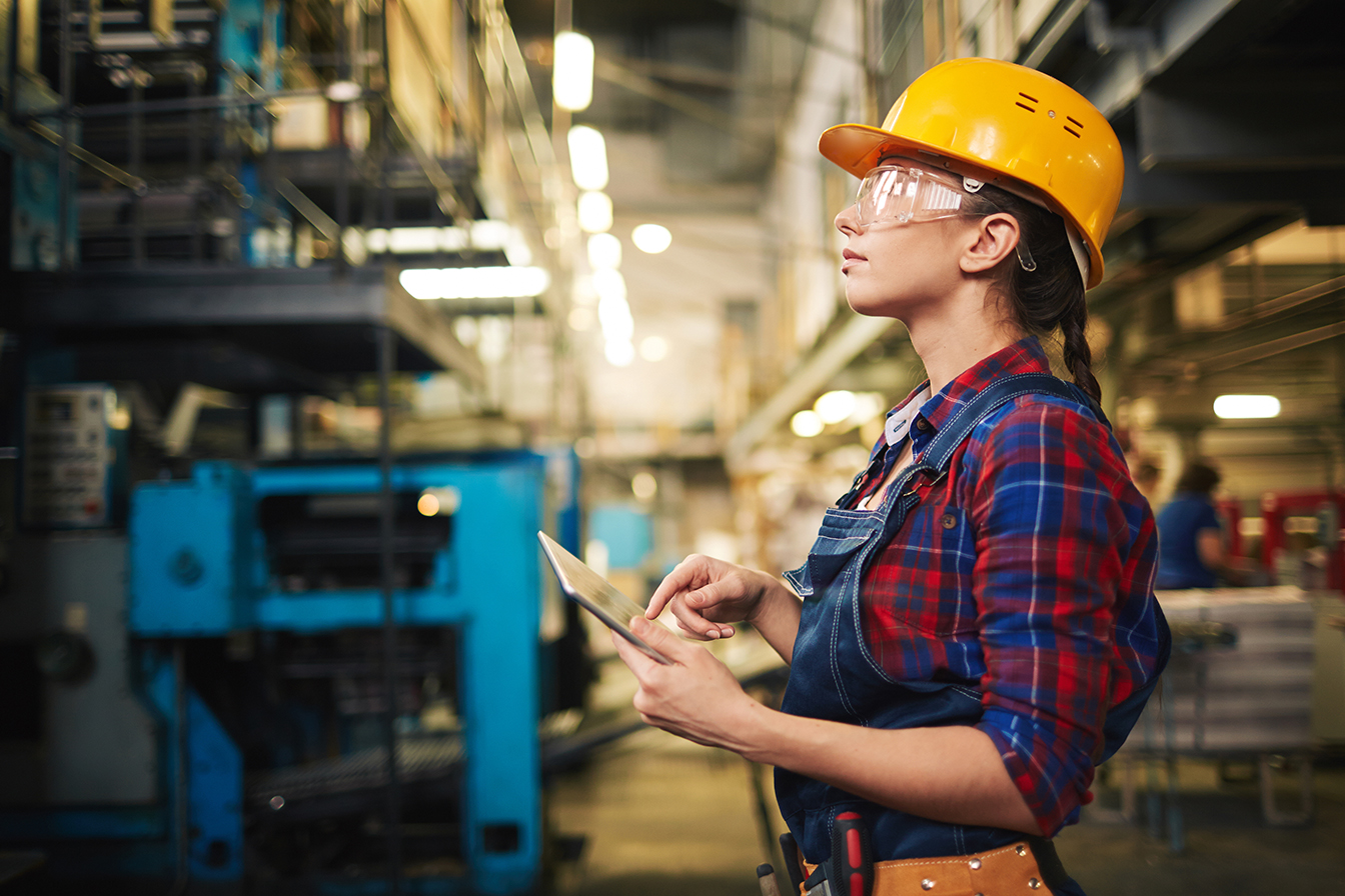 Female Factory Worker Using Tablet and Looking up at Shelves on Plant floor