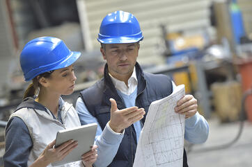 Male and Female Engineers Discussing Data on Plant Floor