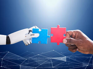 Man and robot hands holding up connecting puzzle pieces