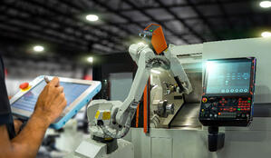 Man with HMI and Robot in factory