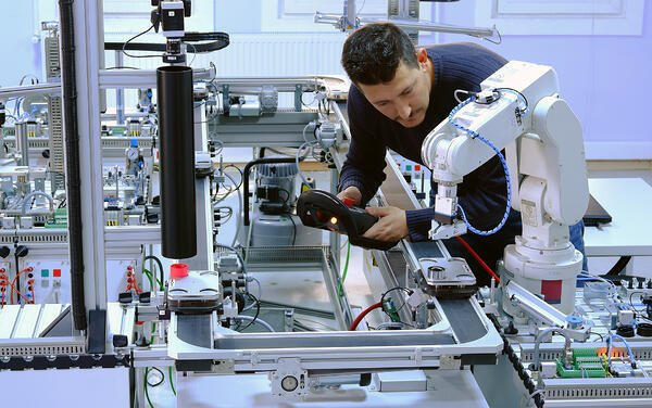 Man working with tabletop robot