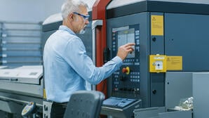 Older Male using HMI screen on a piece of industrial machinery