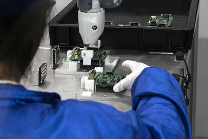 Over shoulder view of man making circuit boards with cobot