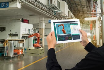Plant Technician with Ipad Operating Robots in a Plant Setting web