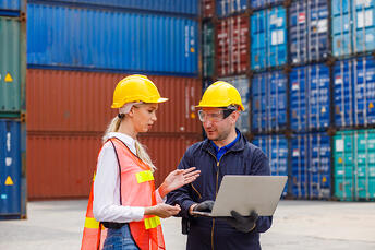 Two workers with computer in front of shipping containers in a port