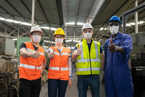 four-manufacturing-workers-thumbs-up-safety-vests