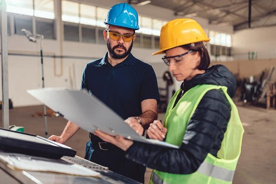 male-female-workers-hardhats-reviewing-plans-on-plant-floor