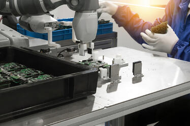 man making circuit boards with cobot