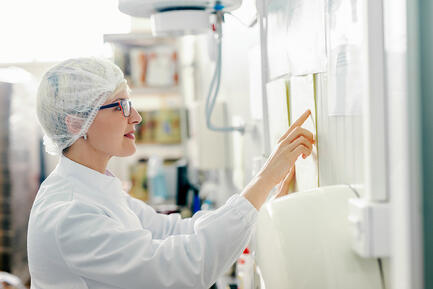 woman-in-white-labcoat-and-hairnet-reading-instructions-on-wall